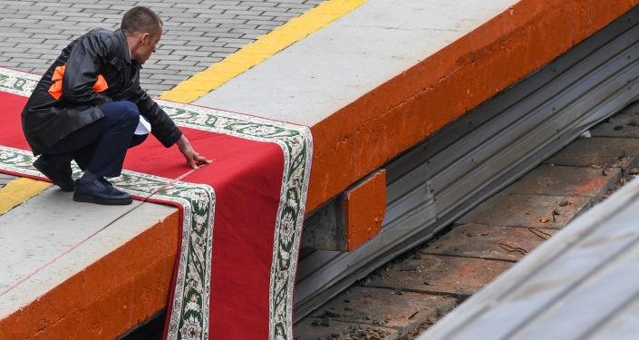 Kim'in treni perona varmadan önce kırmızı halı düzenlemelerini yapmaya çalışan bir görevli