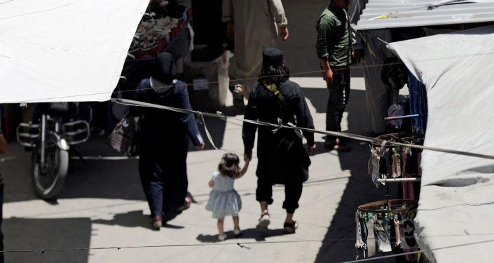 İdlib'in güneyinde eşi ve çocuğuyla pazarda gezen bir cihatçı militan