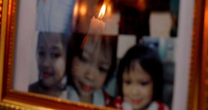 A candle is reflected off framed photos of 3-year-old Myca Ulpina at her wake in Rodriguez, Rizal province, Philippines July 5, 2019. Ulpina was shot during what police said was a sting operation intended to arrest her father, who they said was armed and had used the child as a human shield. REUTERS/Eloisa Lopez