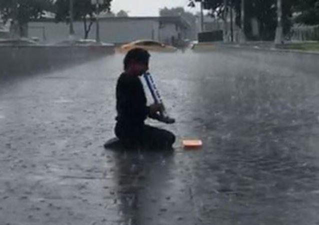 Yağmura aldırmayarak melodikayı çalmayı sürdürdü