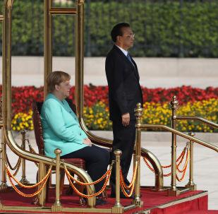 Resmi törenlerde titreme nöbeti geçirmesiyle dikkat çeken Almanya Başbakanı Angela Merkel, Çin Başbakanı Li Keqiang'ın karşılama töreninde Çin milli marşı çalınırken oturdu.