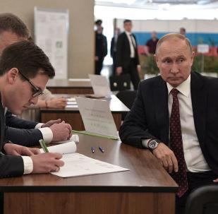 Rusya Devlet Başkanı Vladimir Putin seçim merkezinde yerel seçim komisyonuyla belge doldururken