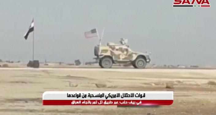 Suriye devlet haber ajansı SANA tarafından yayımlanan Suriye bayrağının yanından geçerek kuzeydoğu bölgesini terk eden ABD zırhlı araçlarının görüntüsü (20 Ekim 2019)