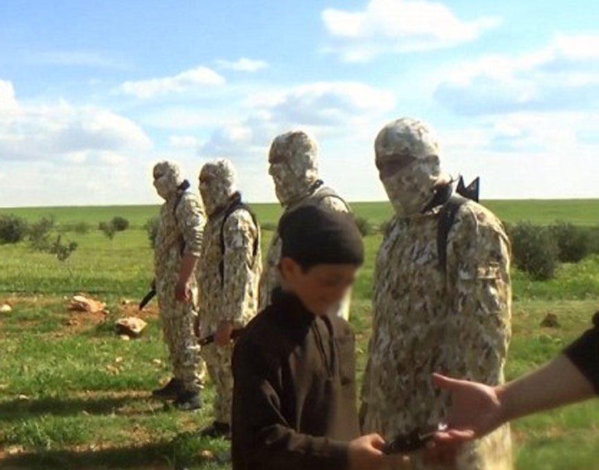 Çocuklardan biri, elindeki bıçağı gülümseyerek maskeli bir militana veriyor.