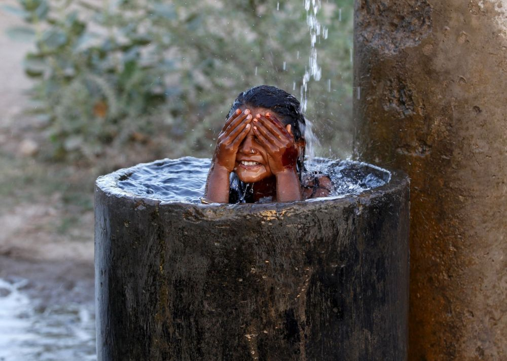 Aşırı sıcaklıkların yaşandığı Hindistan'da bir kız serinlemek için yıkanıyor