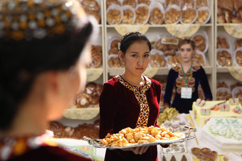 Aşkabat'taki Sergi ve Fuar Merkezi'nde Türkmenistan'ın bağımsızlığının ilan edilmesinin 19. yılı münasebetiyle düzenlenen Ekonomik Başarılar Sergisi'nde misafirleri karşılayan Türkmen kızları