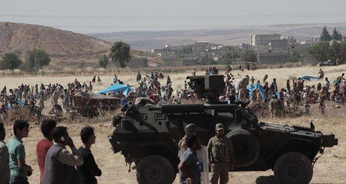 Halep'e bağlı Kobani kentinde (Ayn el Arap), DAEŞ ile bazı Kürt gruplar arasındaki çatışmalardan kaçan bir grup Suriyeli sınırda bekliyor.
