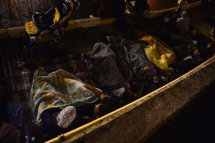 Sığınmacılar ve küçük çocukları, soğuktan etkilenmemek için duvar diplerine serdikleri battaniyelerde uyumaya başladı.