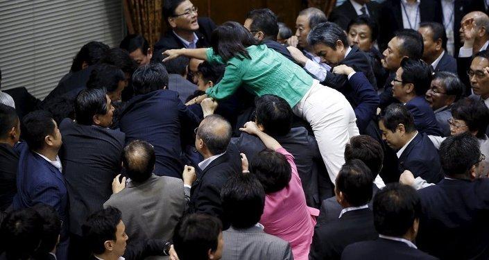 Japonya Parlamentosu'nun üst kanadının silahlı kuvvetlerin yurt dışında savaşa katılmasına onay veren tartışmalı yasayı onayladığı oturumda vekiller birbirine girdi.
