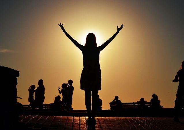 Sivastopol'ün Deniz Sahili'nde genç bir kadın gün batımını izliyor.