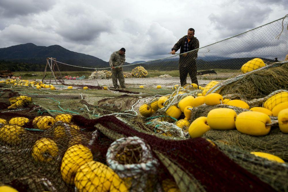 Kuril adaları kıyısında balıkçılar ağlarını tamir ederken.