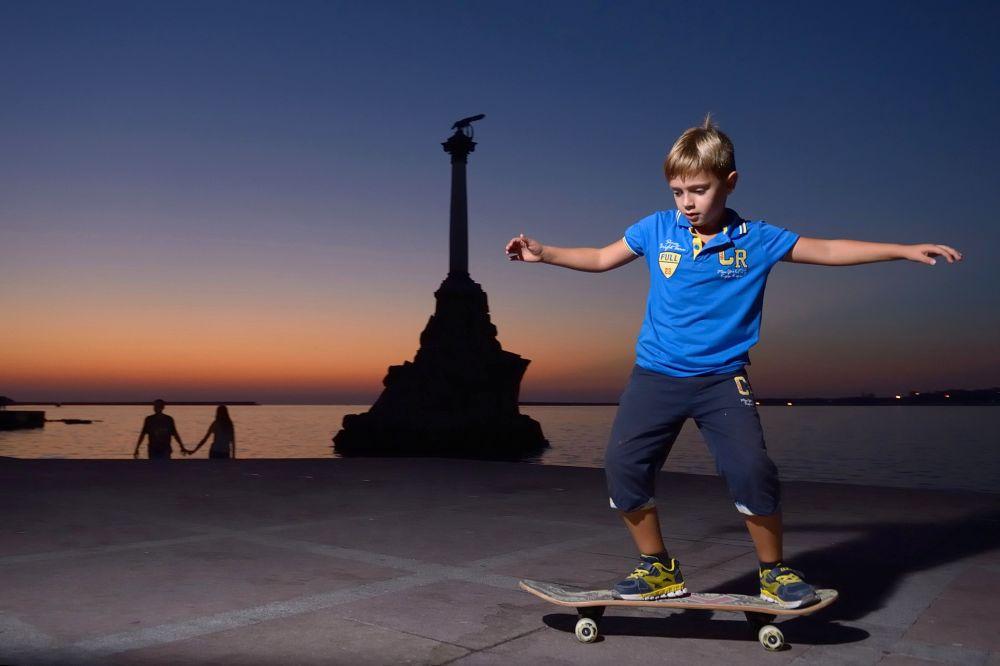 Sivastopol sahilinde kaykay yapan bir çocuk.