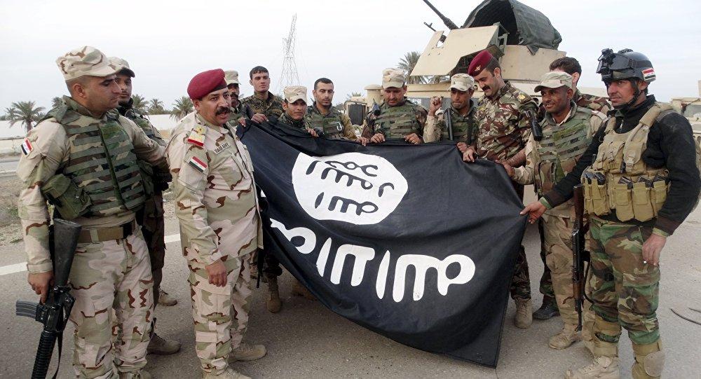 Irak askerleri, IŞİD'den geri aldıkları Ramadi'de bir binadan indirdikleri örgüt bayrağı ile poz verdi