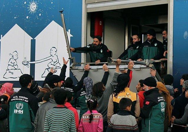 İHH, Suriye'deki kampta evlerinden kaçan Suriyelilere yiyecek dağıtıyor.