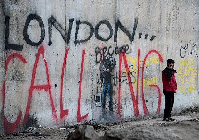 Sığınmacıların İngiltere'ye geçebilmek için bekledikleri Fransa'nın Calais kentindeki 'Jungle' isimli kampta telefonla konuşan bir adam.