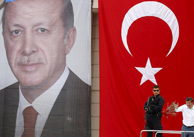 Başbakan Ahmet Davutoğlu, Recep Tayyip Erdoğan'ın posterinin önünde.