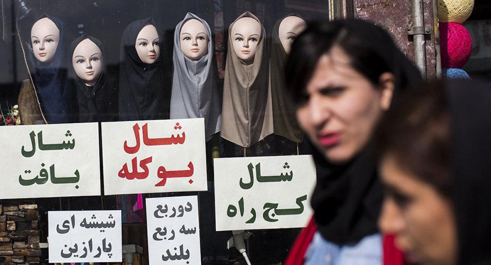 İran'da eşarp satan bir dükkanın önünden geçen kadınlar.