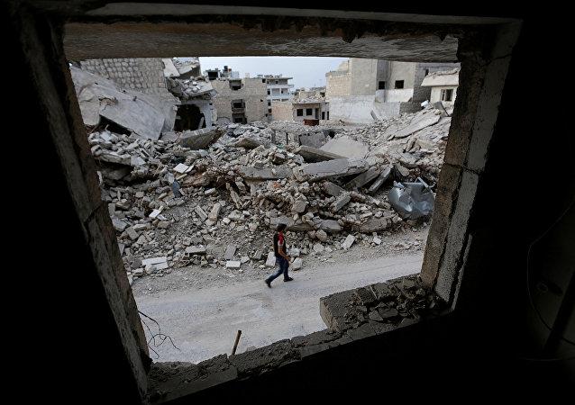 Suriye'nin İdlib kentinde bir adam, 'muhaliflerin' kontrolündeki bölgede yürüyor.