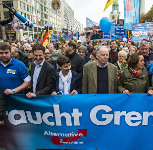 Frauke Petry (3rd, L), chairman of the right-wing populist Alternative for Germany (AfD) party, and the AfD's leading politician Alexander Gauland (4th, L) hold a banner reading Asylum needs limits during a demonstration against the German government's asylum policy organized by the AfD party in Berlin on November 7, 2015.