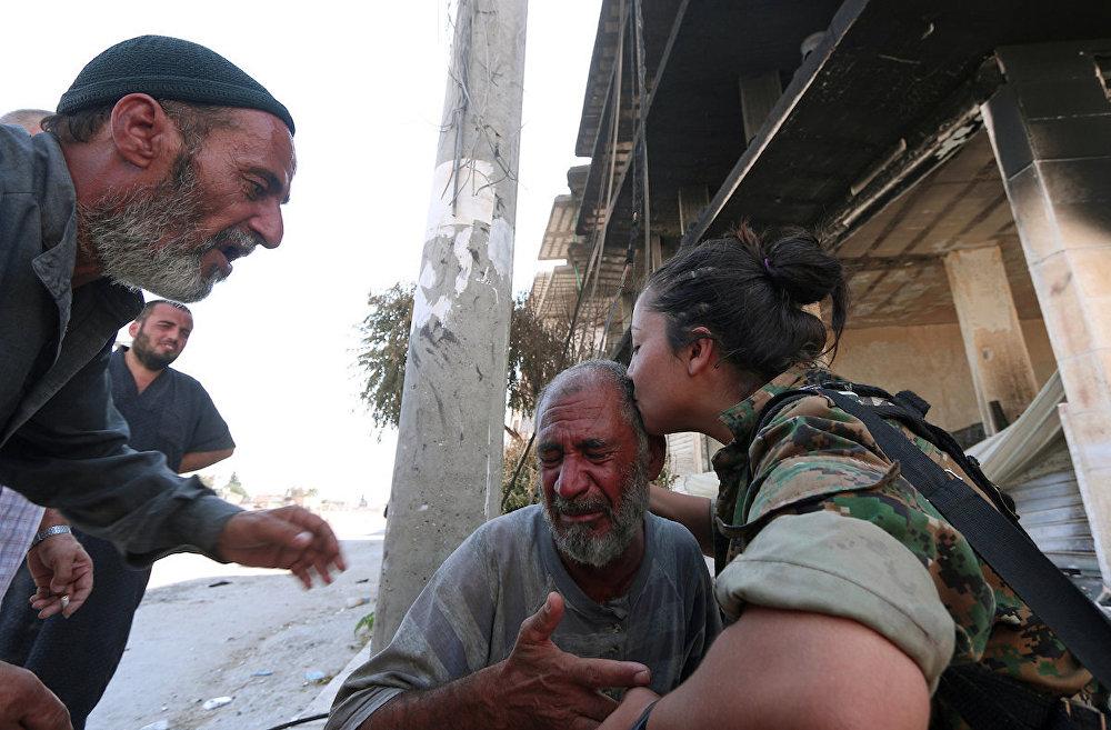 Evlerinden tahliye edilen Menbiçlileri teselli eden Demokratik Suriye Güçleri askeri.