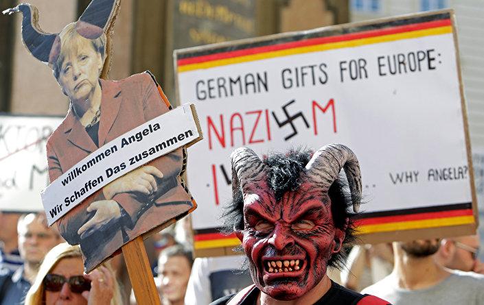 Merkel'i protesto edenler ellerinde 'Almanya'nın Avrupa'ya hediyesi Nazizm ve İslam' ile 'Hoşgeldin Angela, birlikte başarabiliriz' yazılı pankartlar taşıdı.