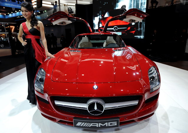 A model poses next to the new Mercedes-Benz SLS AMG displayed at the 31st Bangkok International Motor Show in Bangkok