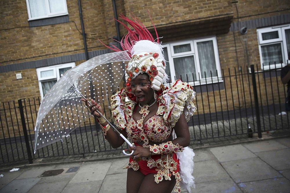 Festival için kostümünü giydikten sonra yağmura yakalanan bir katılımcı.