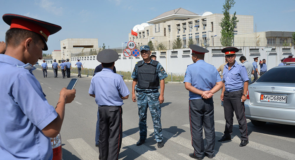 Kyrgyz police officers gather outside the Chinese embassy in Bishkek on August 30, 2016