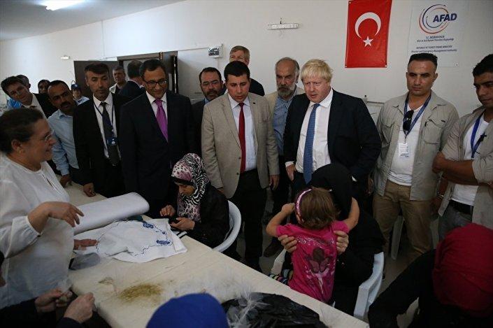 Johnson, alanda bekleyen Suriyelilere nereden geldiklerini sordu, Halep'ten 4 yıl önce Türkiye'ye sığınmak zorunda kalan bir aileyle tercüman aracılığıyla sohbet etti.