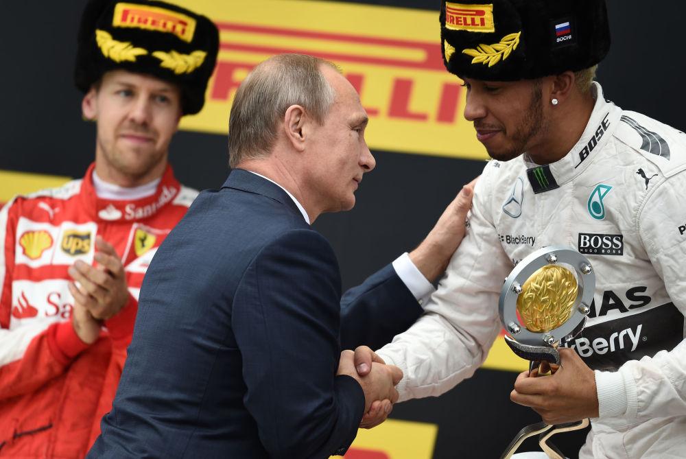 Rusya Devlet Başkanı Vladimir Putin, Formula 1 Soçi Grand Prix'de birinciliği elde eden Mercedes pilotu Lewis Hamilton'a kKupasını takdim ediyor.