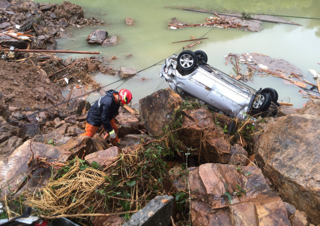 A rescue worker is seen next to an overturned car at the site of a landslide caused by heavy rains brought by Typhoon Megi, in Sucun Village, Lishui, Zhejiang province, China, September 29, 2016
