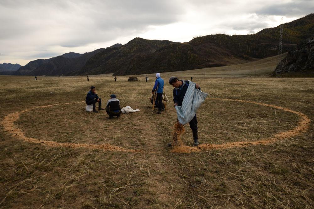 Kok-boru milli oyunun katılımcıları oyun için alanı hazırlıyor ve geken çizgileri çiziyorlar.