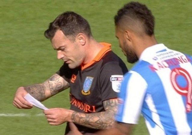 Sheffield Wednesday forması giyen 31 yaşındaki Ross Wallace, rakibinin elinden kâğıdı kapıp okudu.