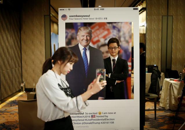 Güney Kore'nin başkenti Seul'deki bir otelde genç bir kadın Trump'ın fotoğrafı ile kendi resmini çekiyor.