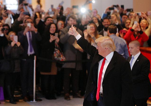Donald Trump, New York Times gazetesinin binasındaki lobide kendisini izleyenleri selamlıyor.
