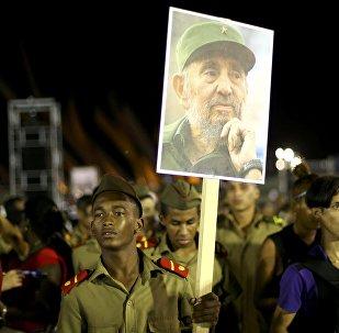 Santiago kentinde Fidel'i anmak için toplanan bir kişi onun fotoğrafını taşıyor
