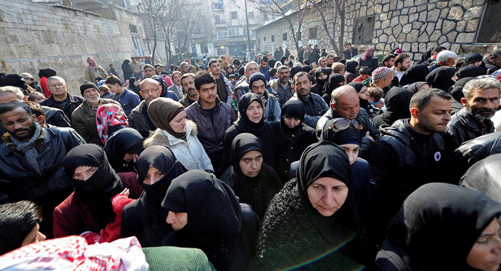 Halep'te kentin doğu kesiminden tahliye edilen akrabalarını ziyaret için bir polis merkezinin önünde bekleyen siviller