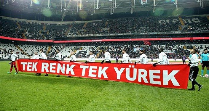 Siyah-beyazlı futbolcular, sahaya üzerinde Tek renk tek yürek yazan pankartla çıktı.