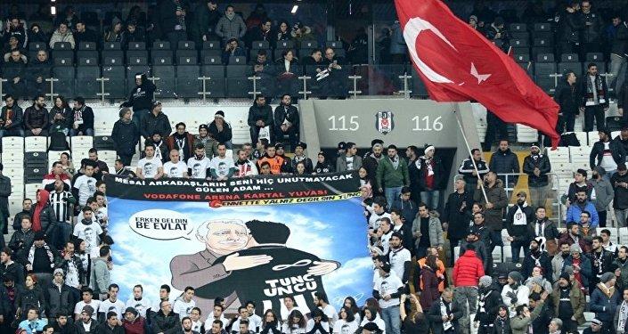 Taraftarlar, İstanbul'daki terör saldırısında yaşamını yitiren Beşiktaş Kulübü'nün Kartal Yuvası mağazası çalışanı Tunç Uncu için pankart açtı.