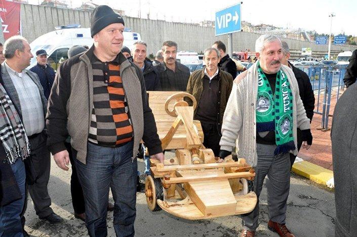 Tahta arabayı, belde yolunu karayolları ağı kapsamına alan Ulaştırma Denizcilik ve Haberleşme Bakanı Ahmet Arslan'a hediye etmek istediklerini söyleyen grubu korumalar içeri almadı. Grup bunun üzerine tahta araba ile VIP önünde bekleyişe başladı.