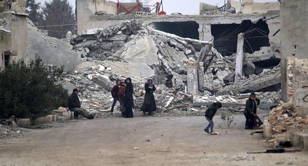 Halep'in kuzetindeki El-Rai'de Suriyeliler bina enkazlarının önünde oturuyor