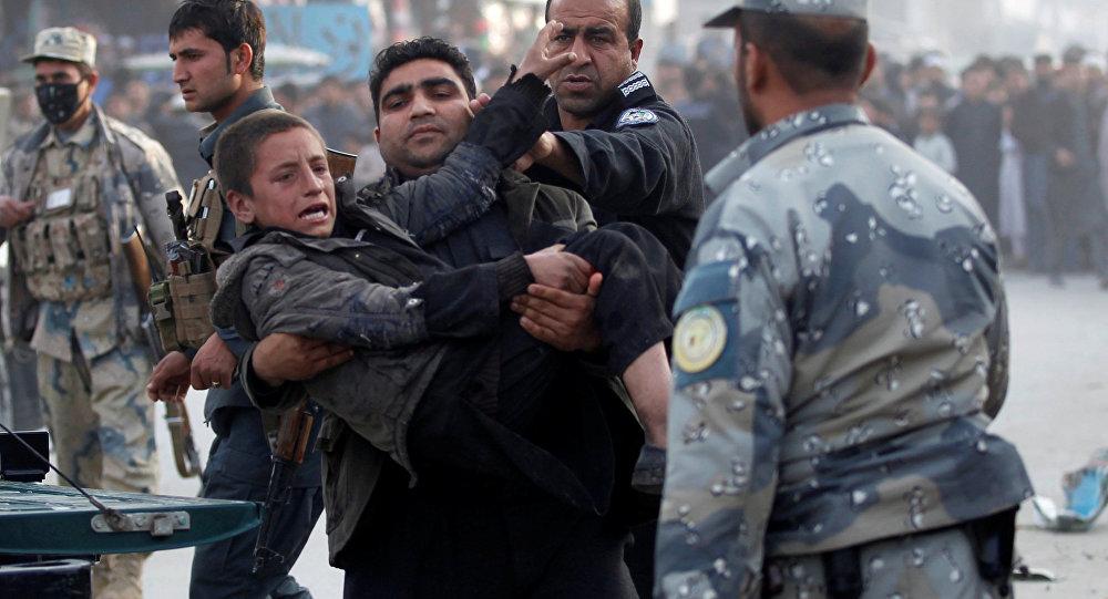 Afgan polisi Celalabad'daki bir bombalı saldırıda yaralanan çocuğu taşıyor