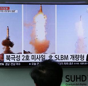 Güney Koreliler televizyondan Kuzey Kore'nin yaptığı balistik füze denemesi ile ilgili haberleri izliyor.