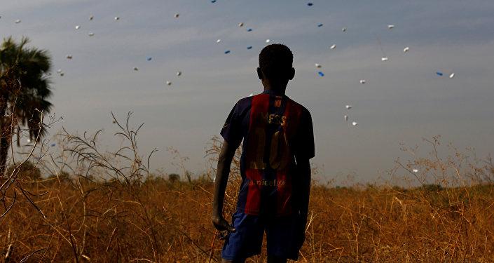 Güney Sudan'da BM Dünya Gıda Programı'nın havadan attığı gıda yardımlarını izleyen bir çocuk