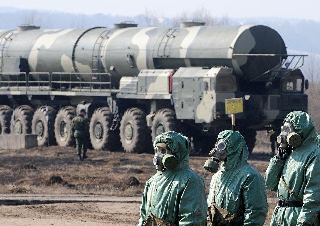 Bir askeri tesiste kimyasal koruma giysileri giyen askerler
