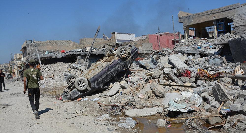 Musul'da şiddetli çatışmalar sonucu yıkılan bina ve zarar gören bir araç