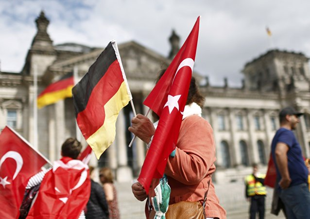 Demonstrators hold Turkish and German flags in front of the Reichstag, the seat of the lower house of parliament Bundestag in Berlin, Germany, June 1, 2016