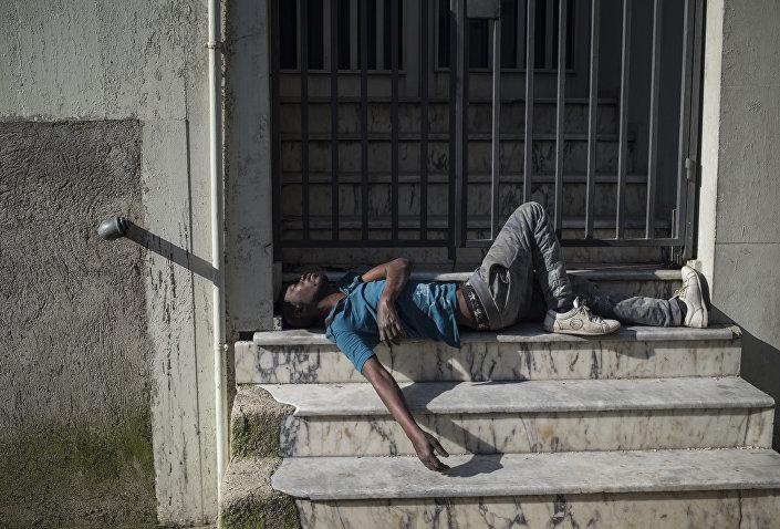 Türkiye ile AB arasındaki sığınmacı anlaşması öncesine göre çok tenha olan Basmane Oteller Sokağı'nda kapalı bir otelin önünde uyuyan bir sığınmacı.
