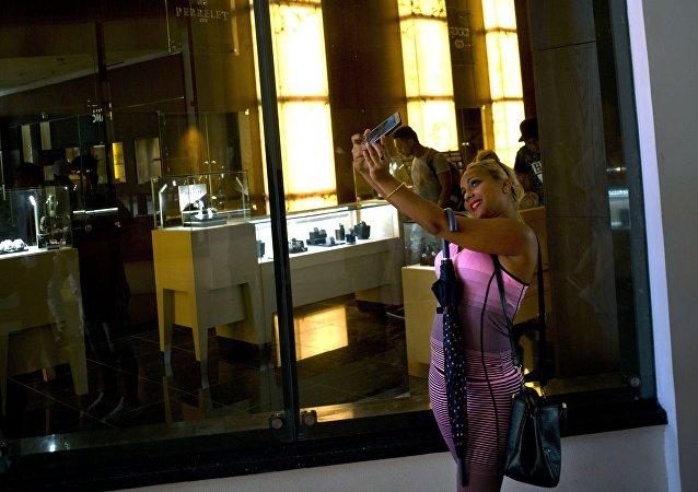 Küba'daki AVM'de satılan ürünlerle selfie çeken bir Kübalı kadın