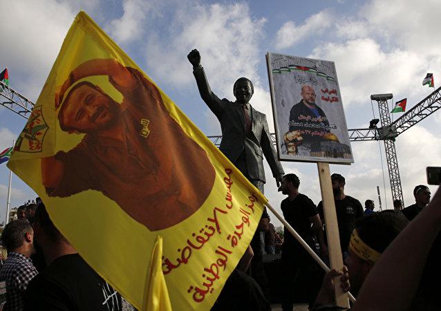 Filistinli eylemciler Ramallah'ta Mervan Barguti'nin fotoğraflarını taşıyarak eylem yaptı